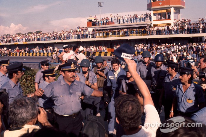 El ganadorJody Scheckter, Wolf Ford, custodiado por la policía