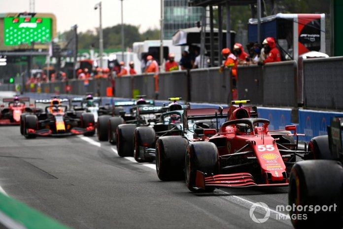 Carlos Sainz Jr., Ferrari SF21, Sebastian Vettel, Aston Martin AMR21, and others in the pit lane