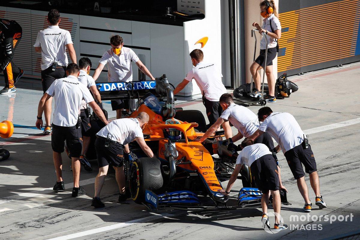 Mechanics push back Daniel Ricciardo, McLaren MCL35M, in garage