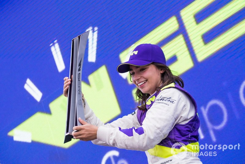 Jamie Chadwick celebrates on the podium with the trophy
