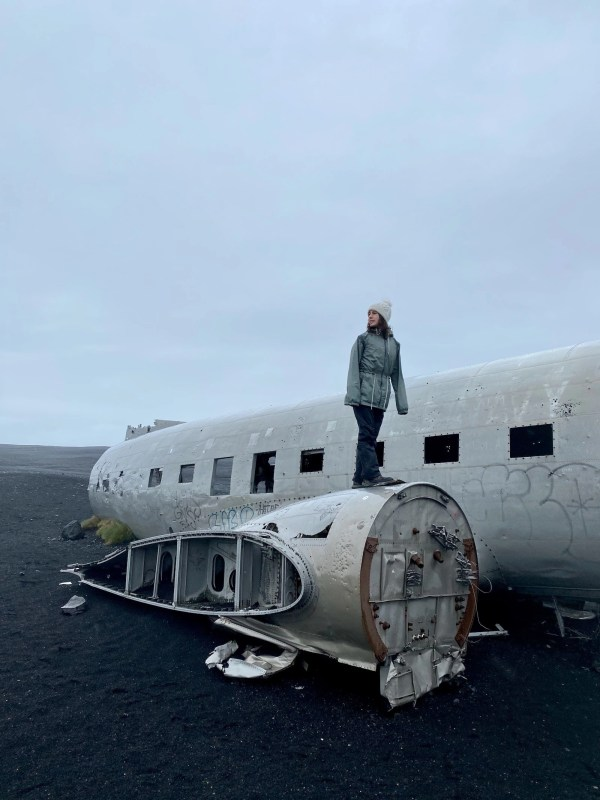 Teen girl standing on top of the famed 1973 plane wreck in Iceland.