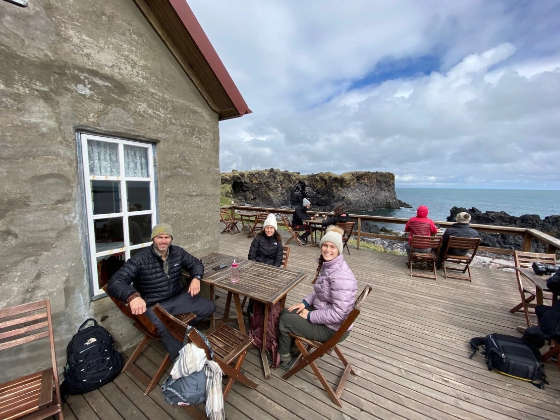 Family sitting at a table outside a cafe overlooking scenic views in Iceland.