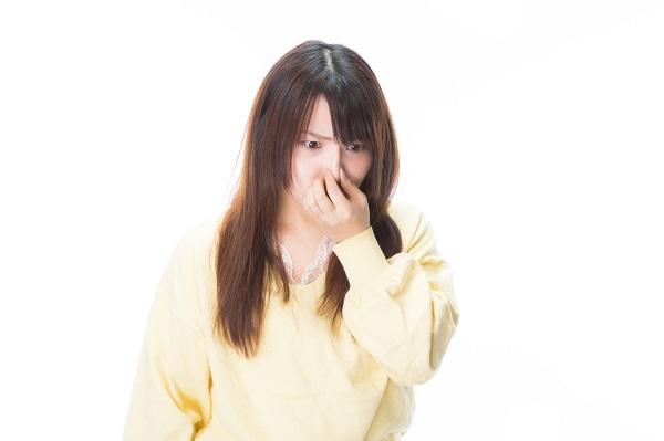 鼻をつまむ清潔感のない女性