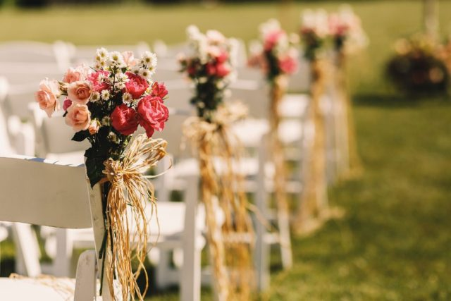 white chairs decorated with pink bouquets for outdoor wedding