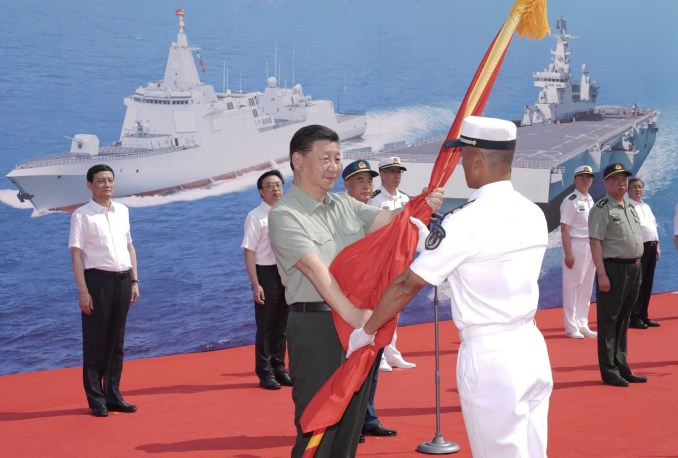 President Xi Jinping presents the PLA flag to the captain of the Long March-18 in Sanya on Friday. Photo: Xinhua