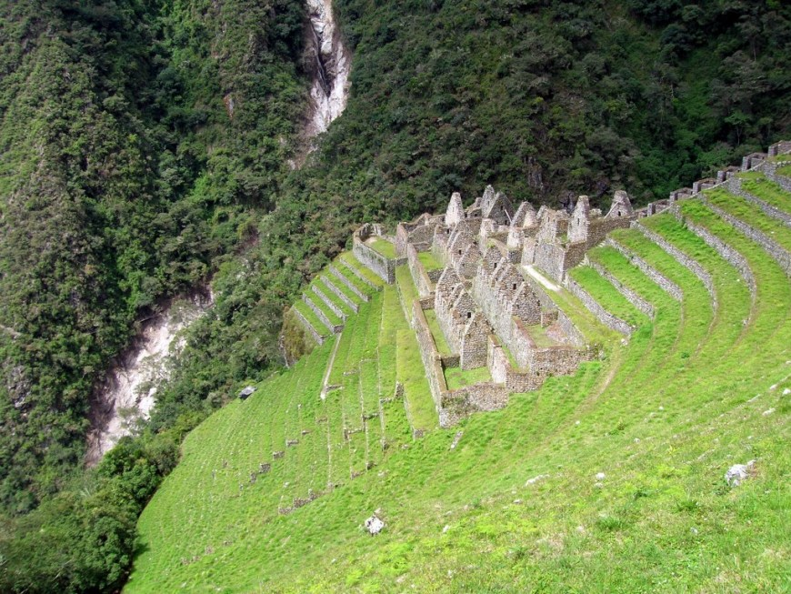 Best Hikes In Peru Image: The hillside has the remnants of old stone buildings; they form peaks but are missing roofs.