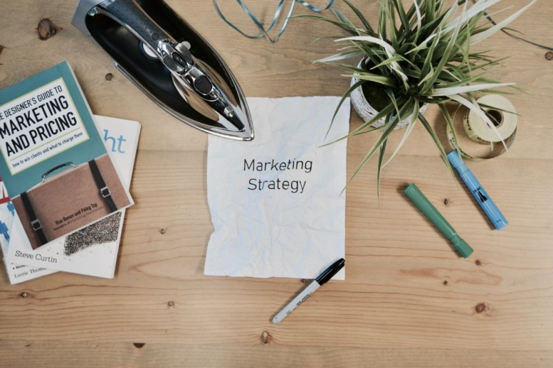 """A sheet of paper with words """"Marketing strategy"""" written on it on the wooden table with some books, flower and a pen."""