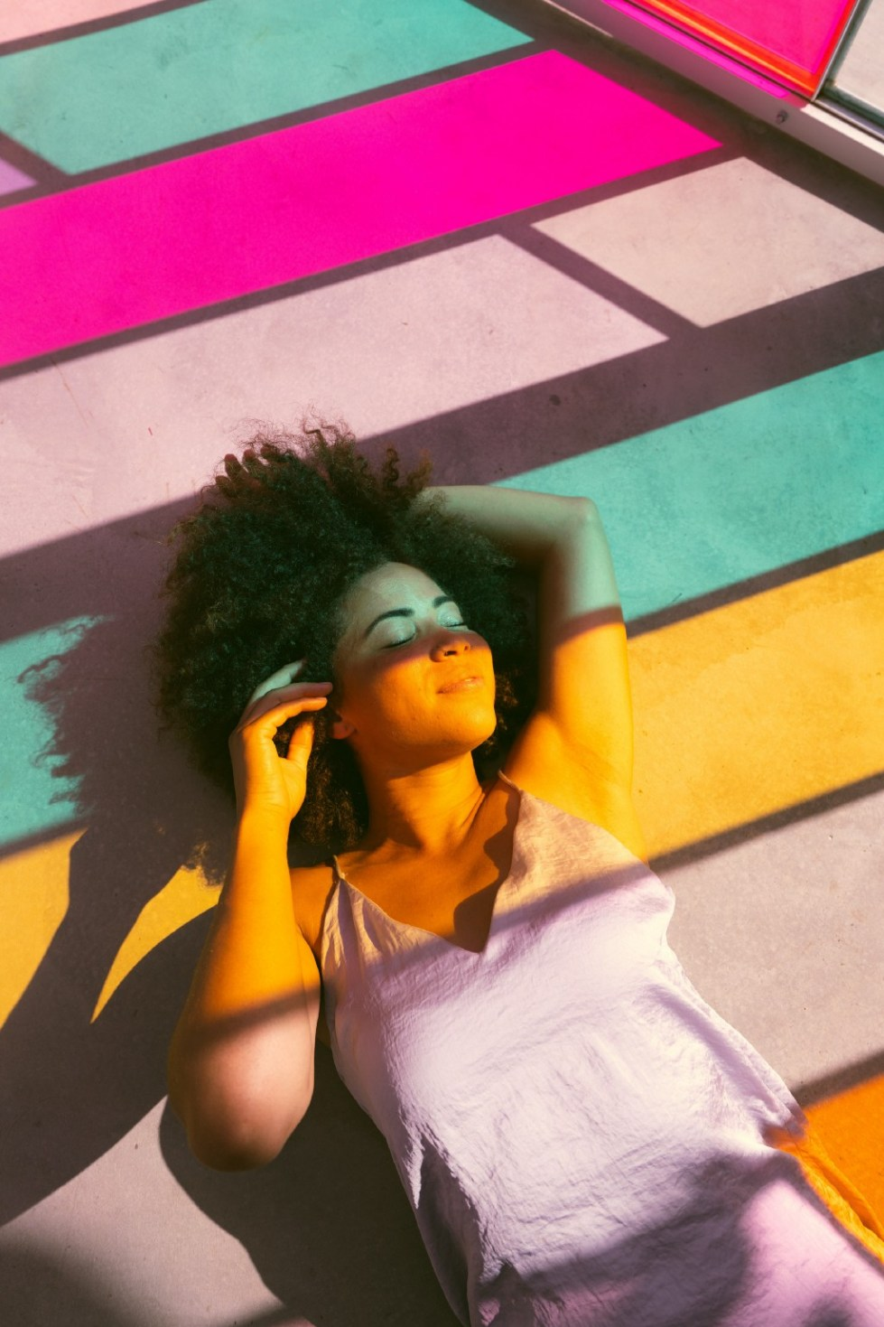 A calm and relaxed woman laying down with colored reflective light shining down on her