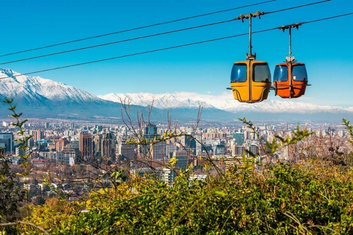Destinations Worth Dreaming Image: An enclosed aerial tram has two pods—one yellow, one orange. They are sailing above the city of Chile; a snow-capped mountain range sits in the background, the city skyline is below, and greenery graces the foreground.