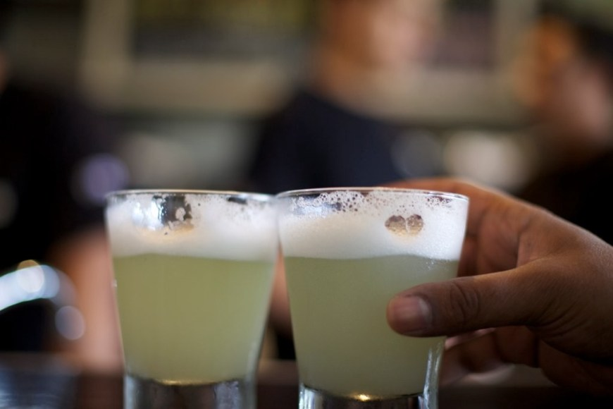 Visit Peru Image: A hand reaches for one of two Pisco sours on a table.