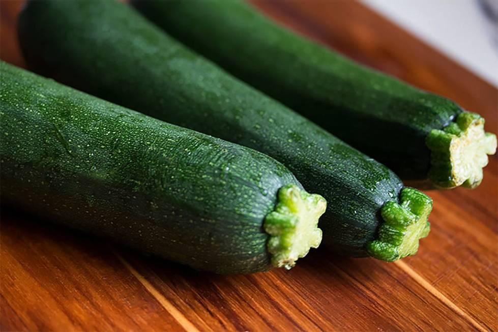 Three zucchinis on a cutting board