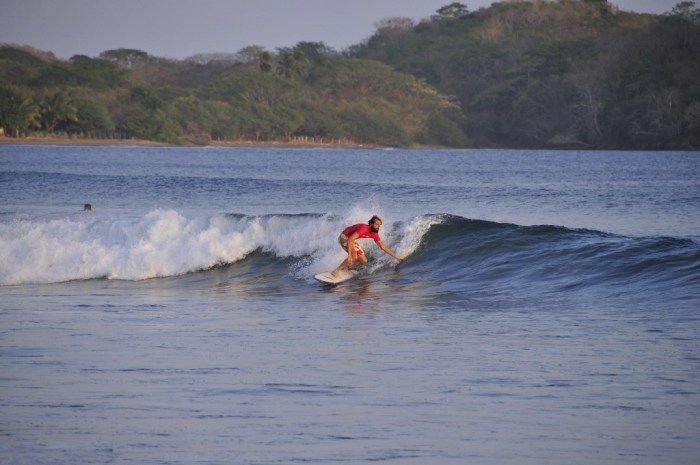 Best Surfing Beaches: A surfer wearing a red wetsuit top and red and white swim shorts rides a surf board, and touches his hand to a cresting wave.