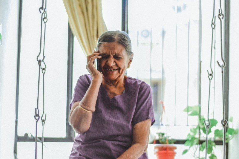 A smiling old lady sitting next to the window and having a phone call.
