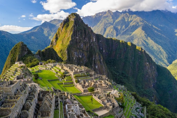 Central and South American Ruins Image: A beautiful view of Machu Picchu reveals this Central and South American ruin to be a vision of green and brown mountains, a grey aged village, and a blue sky dappled with white clouds.