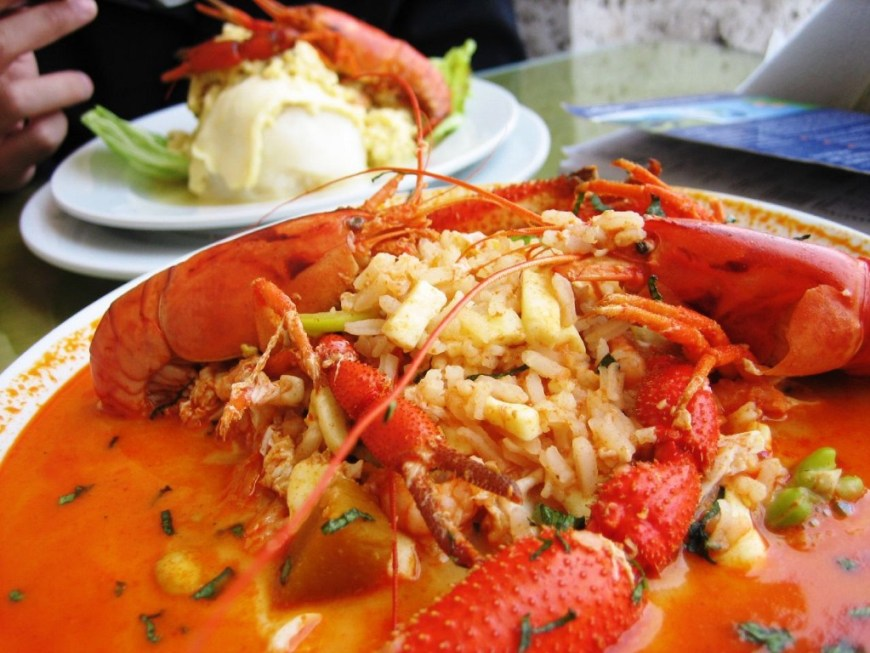 Visit Peru Image: The vibrant red seafood soup is piled onto a white dish; a generous scoop of rice has been placed in the middle of the dish.