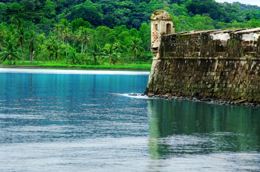 Architecture In Panama Image: A fort aged and in the early stages of being reclaimed by natures has openings which overlook calm blue waters, and a vivd green forest.