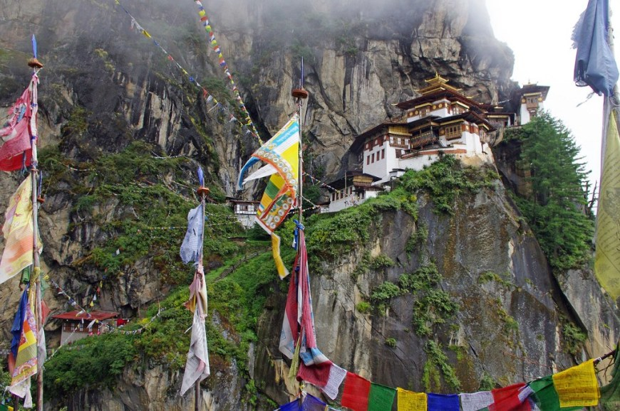 Destinations Worth Dreaming Image: Colourful flags and fabrics are suspended throughout as we see buildings leading up a mountainside.