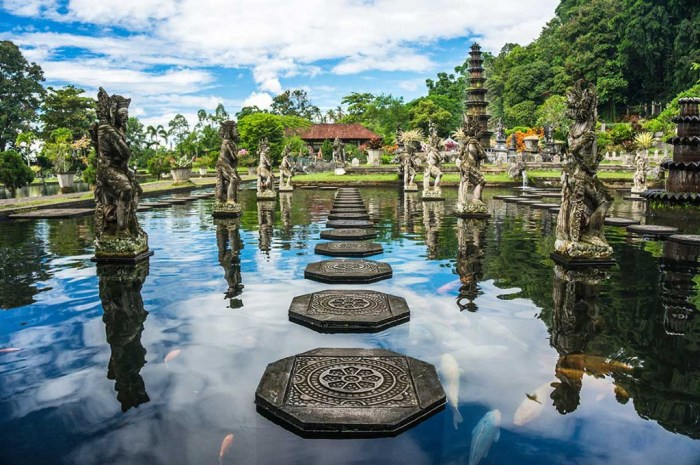 Destinations Worth Dreaming Image: A series of carved steps make a path, and is surrounded by statues. In this water feature swim koi fish. Pagodas and trees are seen along the edge.