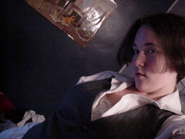 [2006/2007, Freshman in college: Kirsten is taking a selfie; she is wearing a white button up dress shirt with a grey waistcoat and white lacy bra; she has short dark hair and is standing in front of a dark blue wall with an abstract art poster]