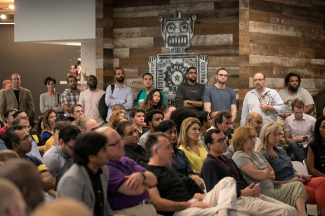 Image: A large crowd of people are standing and sitting inside while attending an event held at Capital Factory in Austin. TX.