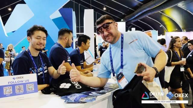 DELTA Summit OKEx Malta Tech Week —A happy visitor at OKEx's booth at DELTA Summit