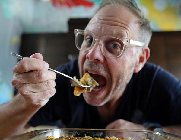 Celebrity Chef Alton Brown eating a big hunk of cornbread dressing
