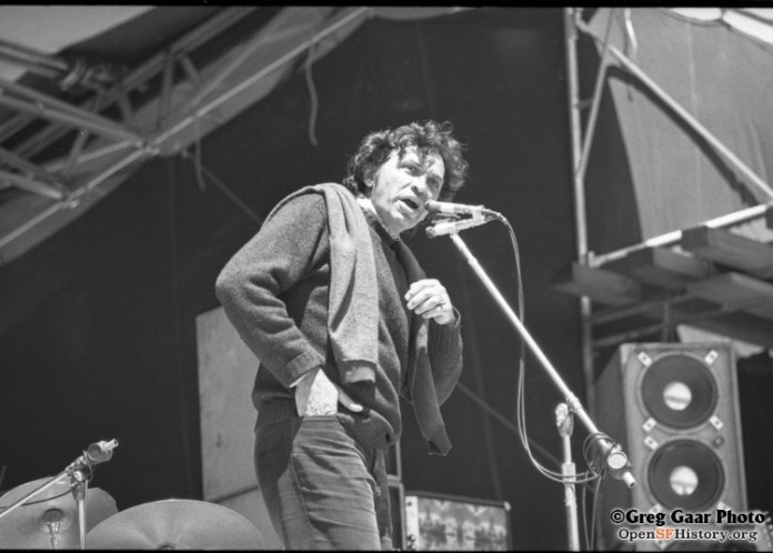 Black and white photo of Bill Graham talking into a microphone onstage at Kezar.