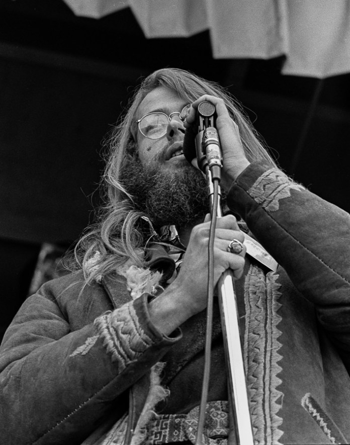 Black and white portrait of Chet Helms talking into a microphone on stage.