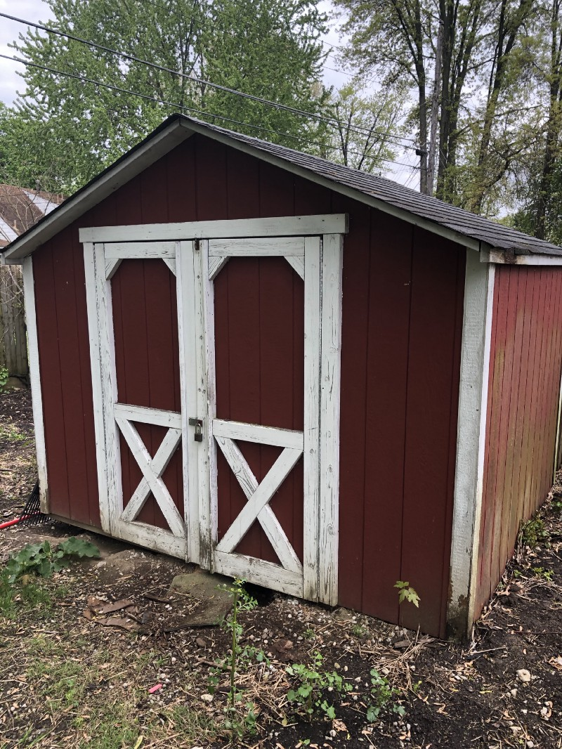 This is a picture of a large red shed with white accents and a lock on the door.