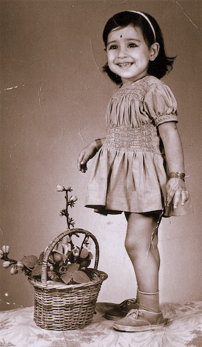 Description: A sepia toned pictured of Abha as a toddler. She is wearing a dress and stands smiling at the camera. By her feet we see a basket of flowers.