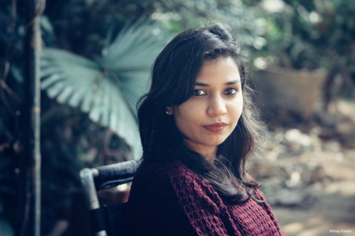 Description: A photograph of Preeti. She wears a dark red sweater and looks boldly at the camera