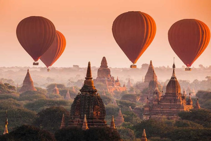 Destinations Worth Dreaming Image: Four rust coloured hot-air balloons float past the Myanmar skyline.