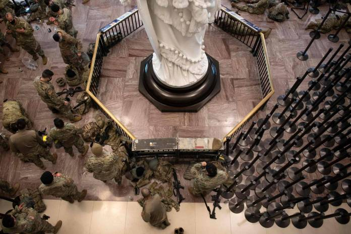 Members of the National Guard rest in the Capitol Visitors Center on Capitol Hill in Washington on Wednesday, ahead of a House vote to impeach U.S. President Donald Trump. | AFP-JIJI