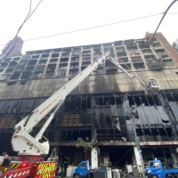Emergency personnel work at the scene of an overnight fire on Thursday that tore through a building in the southern Taiwanese city of Kaohsiung.   CNA PHOTO / VIA AFP-JIJI