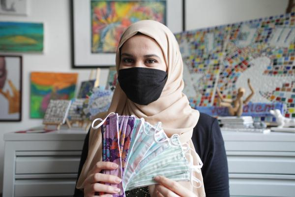 Woman in hijab holding face masks.