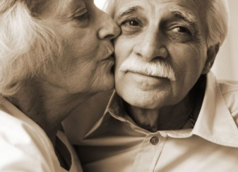 Black and white portrait of an elderly woman kissing her husband's cheek