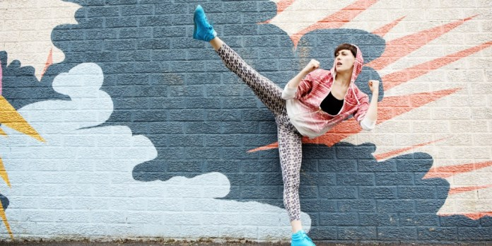 Woman Kicking Leg Up In Front of Graffiti Wall
