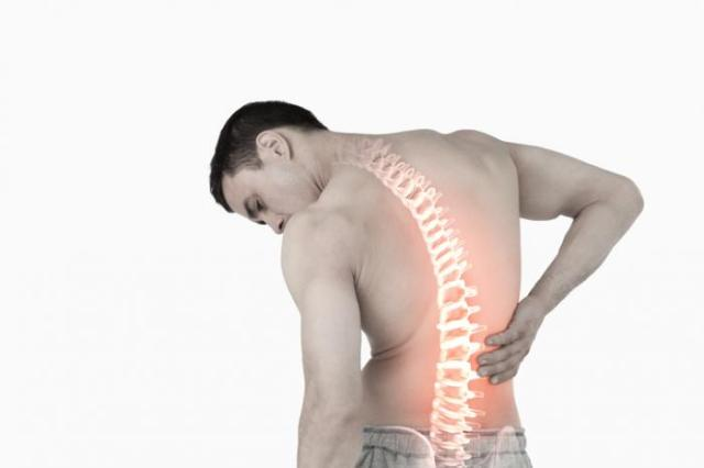 A man with visible spine holds his back.