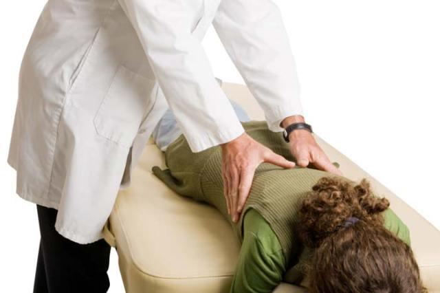 Хиропрактик работает на спине пациента