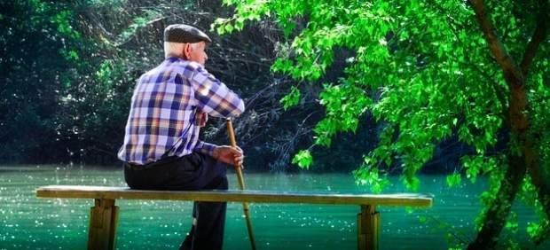 Un anciano, sentado en un banco.