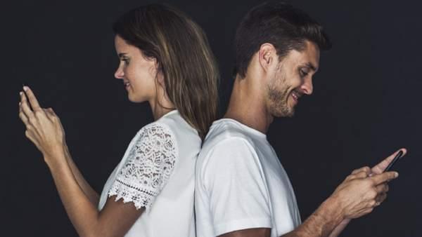 Dos jóvenes, con sus dispositivos móviles.