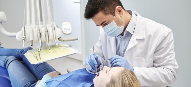 Un dentista atiende a una paciente.
