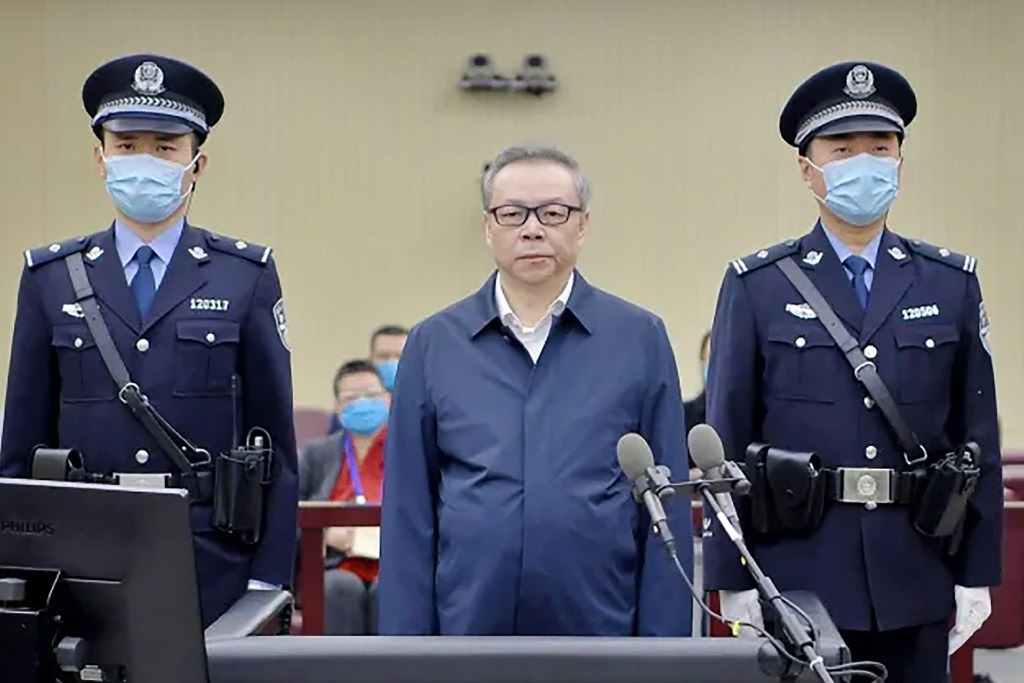 This handout photo taken on 11 August 2020 and released by the Second Intermediate People's Court of Tianjin, shows Lai Xiaomin (C), former chairman of China Huarong Asset Management Co., standing during his trial.