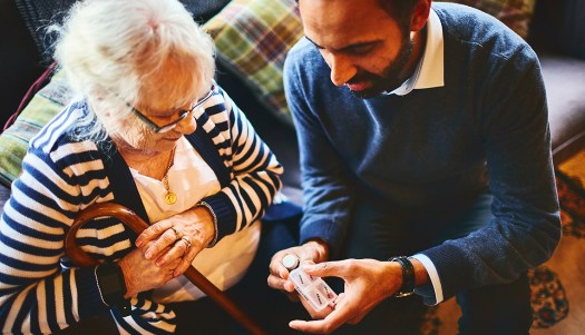Son explaining medicine dosage to his elderly mother