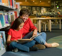 Grandmother and granddaughter reading library book