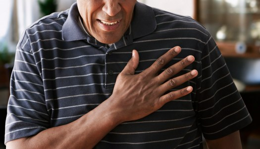 Man holds hand to chest, pained expression