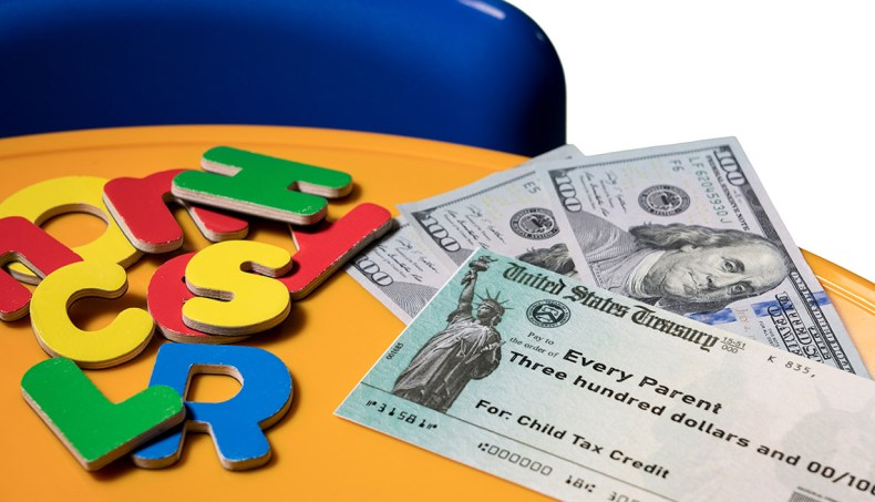 US Treasury illustrative check for child tax credit on table with 3 hundred dollar bills and colorful letters