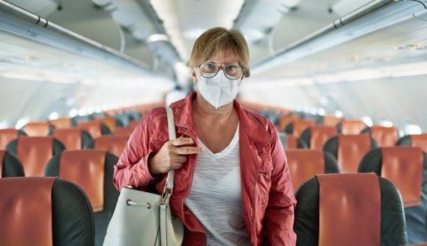 Mujer con máscara viaja en un avión comercial