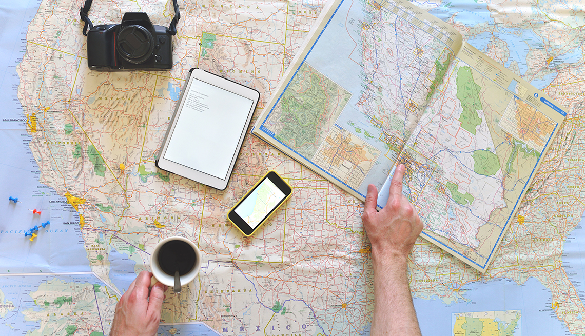 Travel Apps for Road Trips You Must Download Now Man Looking at Maps and Using Electronic Devices  Road Trip Planning Apps   Travel
