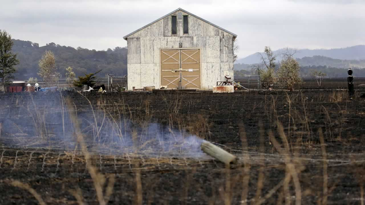 A barn stands undamaged while surrounded by blackened grasses and in view of still smoldering fence posts Monday, Sept. 14, 2015, near Middletown, Calif. <span class=meta>AP Photo/Elaine Thompson</span>